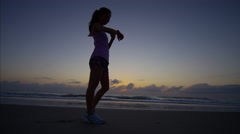An Asian Chinese female at dawn on beach by the sea doing cardio training Stock Footage