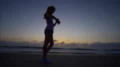 A slim healthy ethnic American woman in athletic sportswear by the ocean Stock Footage