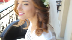 Happy bride turning around with a veil on the balcony - stock footage