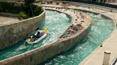 Aquapark. Tourists in canoe on extreme rafting in artificial rowing channel - stock footage