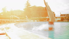 Young man in summer day is diving into outdoor swimming pool dolly Stock Footage