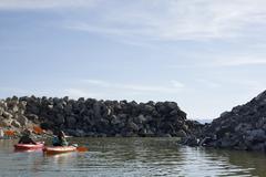Rear view of kayakers sitting on water in kayaks facing rocks, Great Salt Lake, - stock photo