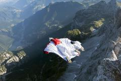 Two male BASE jumpers wingsuit flying from mountain, Dolomites, Italy Stock Photos