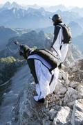 Two male BASE jumpers preparing to launch from mountain, Dolomites, Italy Stock Photos