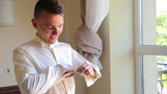 The groom cufflinks boutonniere near the window Stock Footage