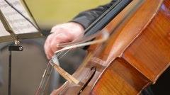 Cellist playing cello, close up, blurred defocused background Stock Footage
