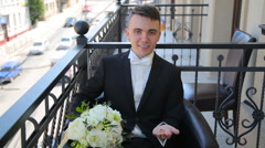 Groom with wedding bouquet and rings sitting on a balcony and smiling Stock Footage