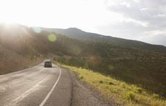 Rear view of car traveling on rural road near Torrey, Utah, USA - stock photo