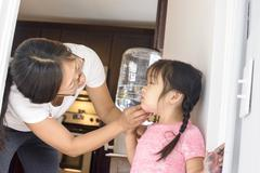 Mother wiping daughter's face - stock photo