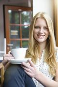 Young woman with long blond hair sitting holding coffee cup, looking at camera - stock photo