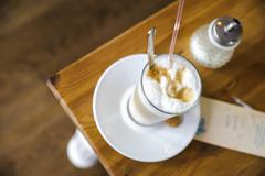 High angle view of frothy latte and sugar dispenser on table - stock photo