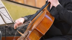 Cellist playing cello, close-up, defocused background - stock footage