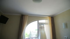Wedding bride's dress hanging on a window - stock footage