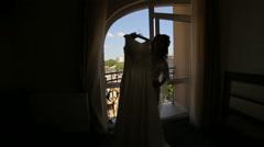Happy bride is dancing with wedding dress in the dark room - stock footage