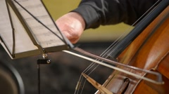 Cellist playing cello and leafing through notes,  close-up Stock Footage
