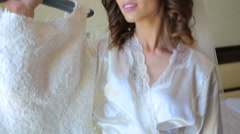 Beautiful bride is embracing wedding dress and smiling - stock footage