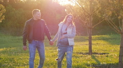 Lovers walking in a field at sunset Stock Footage