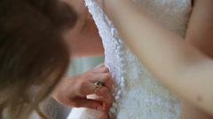 Best friend helps to the bride to clasped a wedding corset Stock Footage