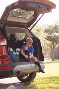 Boy football player sitting in car boot tying football boot laces Stock Photos