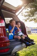 Boy and younger sister sitting in car boot eating oranges on football practice - stock photo