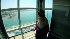 Female lady get down in a glass lift elevator to the sea beach Stock Footage