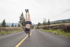 Young woman doing one handed handstand in road - stock photo