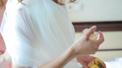 Bride's friends help to wear wedding dress, when she hold the parfume Stock Footage