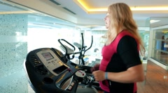 Gym. Woman lady female runs on a treadmill. Cardio Workout. Overweight, not fat Stock Footage