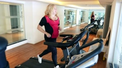 Gym. Woman female runs on a treadmill. Cardio Workout. Overweight, not fat Stock Footage