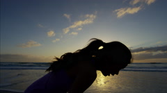 Healthy Chinese female in athletic sportswear resting on the beach at sunrise Stock Footage
