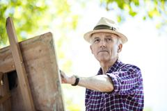 Senior man drawing in park, Hackney, London - stock photo