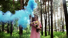 Beautiful girl in a forest in blue from a color smoke grenade - stock footage