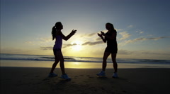 Female friends running on beach at sunrise with wearable technology Stock Footage