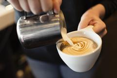 Coffee shop barista pouring milk into coffee, mid section, close-up - stock photo