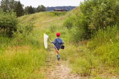 Young boy walking through field, carrying fishing net, rear view Stock Photos