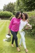 Mother and grown daughter in garden together Stock Photos