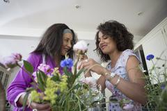 Mother and grown daughter in kitchen, arranging flowers Stock Photos