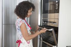 Mid adult woman in kitchen, using oven Stock Photos