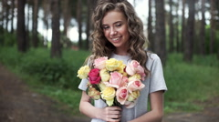 Portrait of a beautiful young woman with a bouquet of flowers in her hands - stock footage