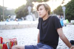 Young man sitting looking out from beach, Javea, Spain - stock photo
