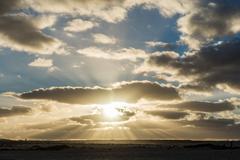 Sunset shining through the clouds on the Spanish island of Fuerteventura Stock Photos