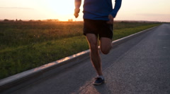 The athlete jogs at sunset - stock footage