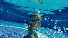 Male swimmer diver rises up the surface of pool water. Underwater slow motion Stock Footage