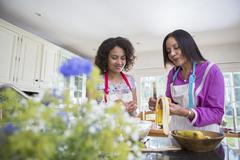 Mother and grown daughter, cooking in kitchen - stock photo