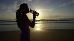 Asian Chinese girl resting and rehydrated on the beach after running routine Stock Footage