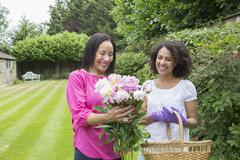 Mother and grown daughter gathering flowers in garden - stock photo