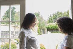 Mother and grown daughter, standing by patio door, talking Stock Photos