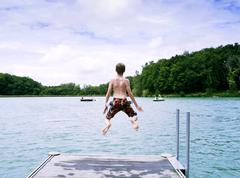 Rear view of boy wearing swimming shorts jumping into lake, Tilac, South West Stock Photos