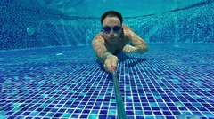 Male swimmer diver swims under water in the pool. Underwater slowmotion Arkistovideo