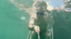 Male swimmer diver swims under water in the sea. Underwater survey selfie Arkistovideo